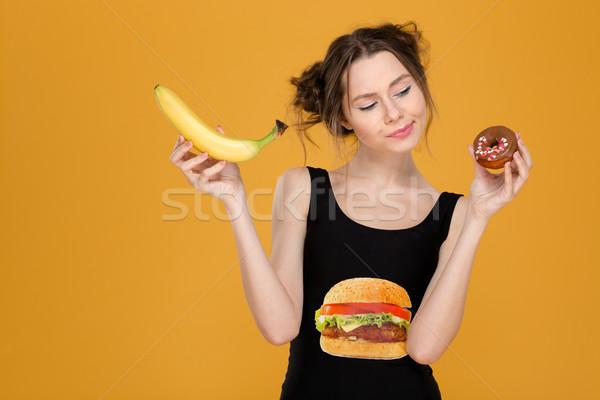 Confuso mulher jovem escolher saudável alimentos não saudáveis Foto stock © deandrobot