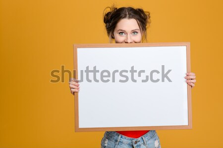 Smiling cute lovely young woman hiding behind blank board Stock photo © deandrobot