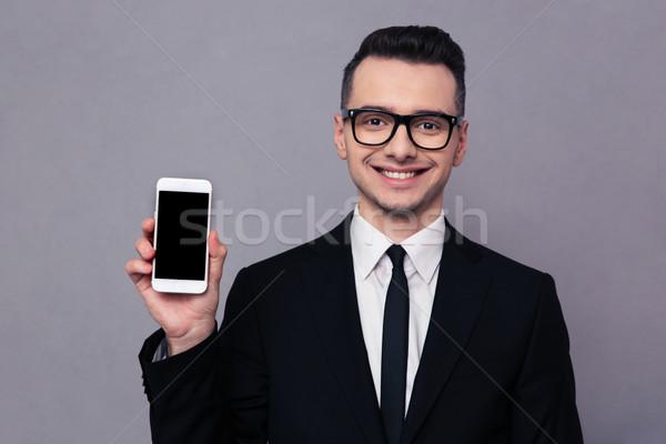 улыбаясь бизнесмен смартфон экране портрет серый Сток-фото © deandrobot
