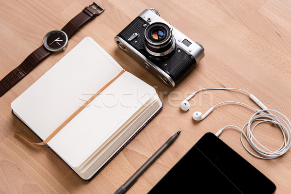 Notepad, tablet, earphones, camera watch and pen on wooden table Stock photo © deandrobot