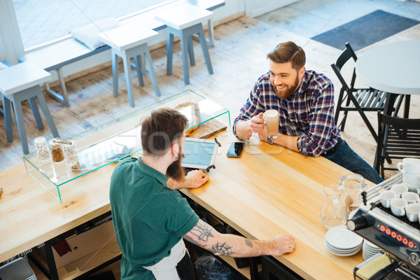 Cheeful man drinking coffee in cafeteria and talking to barista Stock photo © deandrobot