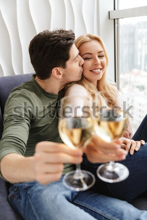 Happy couple drinking red wine and flirting at home Stock photo © deandrobot
