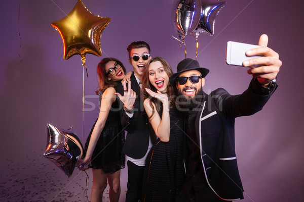 Cheerful friends smiling and making selfie together  Stock photo © deandrobot