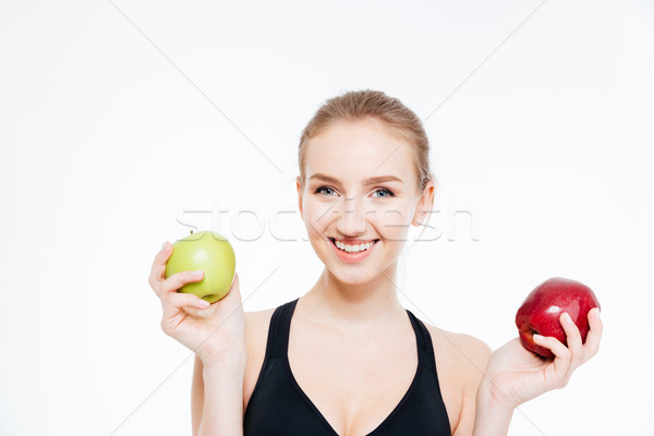 Happy beautiful sportswoman holding green and red apples  Stock photo © deandrobot