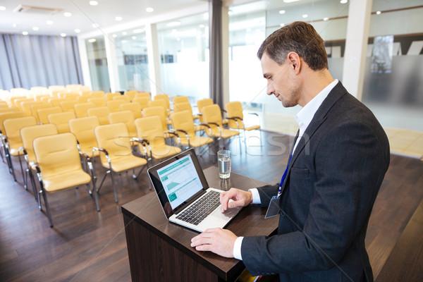 Koncentrált hangszóró áll laptopot használ fekete öltöny üres Stock fotó © deandrobot