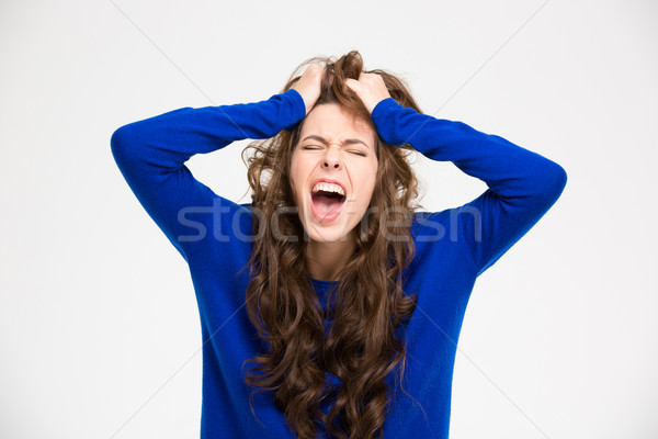 Angry crazy young woman with long curly hair screaming  Stock photo © deandrobot