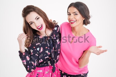 Two amazed young women with opened mouths pointing away Stock photo © deandrobot