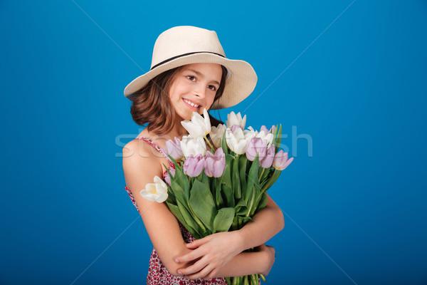 Derűs csinos kislány kalap tart virágcsokor Stock fotó © deandrobot