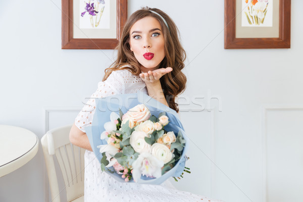 Cute woman holding bouquet of flowers and sending a kiss  Stock photo © deandrobot