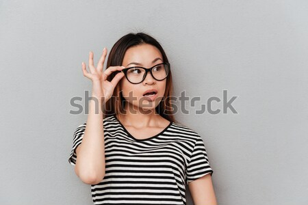 Amazed charming teenage girl in glasses with mouth opened over  Stock photo © deandrobot