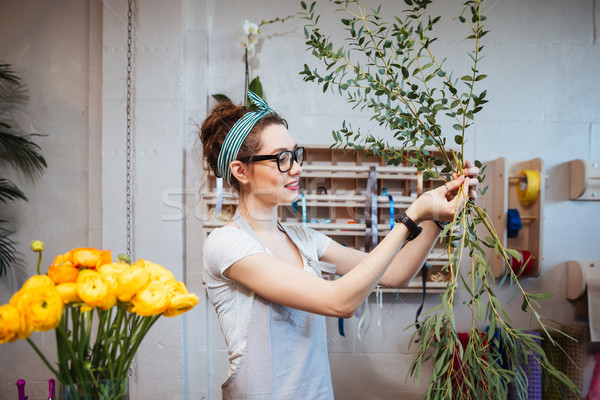 Smiling lovely young woman florist arranging plants in flower shop Stock photo © deandrobot