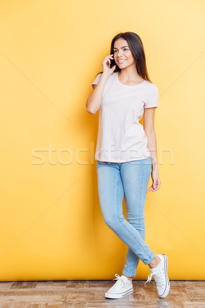 Happy woman talking on the phone and looking away Stock photo © deandrobot