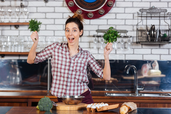 Cheerul woman holding dill and parsley on the kitchen Stock photo © deandrobot