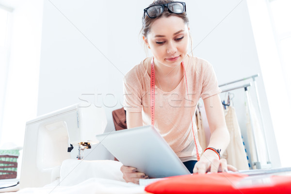 Serious woman seamstress with tablet working in workshop Stock photo © deandrobot