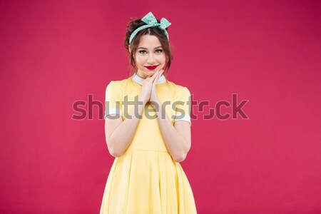 Smiling attractive pinup girl in yellow dress showing sweet lollipop Stock photo © deandrobot