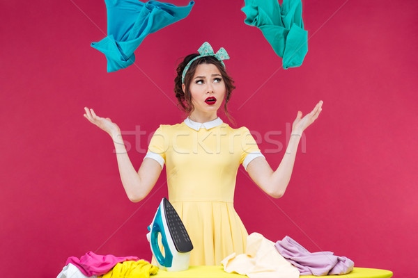 Pretty upset woman with iron throwing clothes in the air Stock photo © deandrobot
