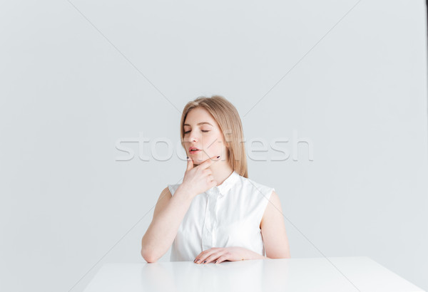 Young woman with closed eyes sitting at the table Stock photo © deandrobot