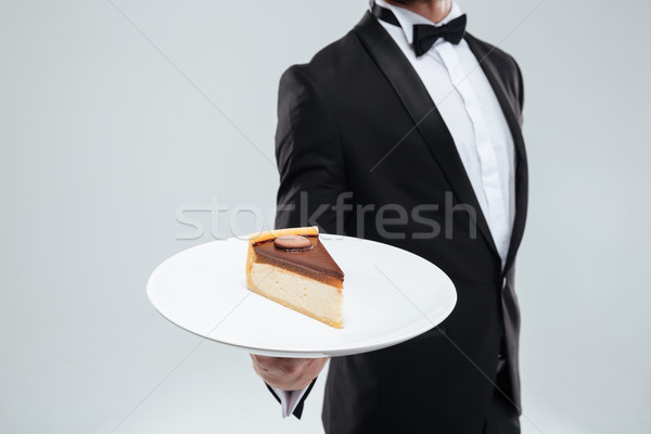 Waiter in tuxedo holding plate with piece of cake Stock photo © deandrobot