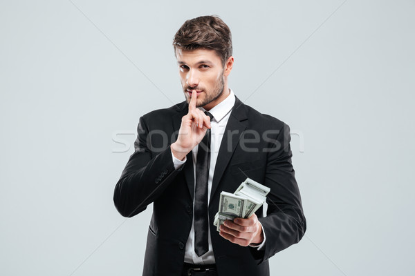 Handsome young businessman holding money and showing silence sign Stock photo © deandrobot
