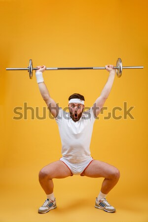 Cheerful man athlete sitting with legs crossed and pointing up Stock photo © deandrobot