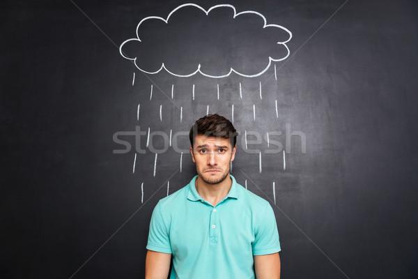 Sad man standing under the rain drawn on blackboard background Stock photo © deandrobot