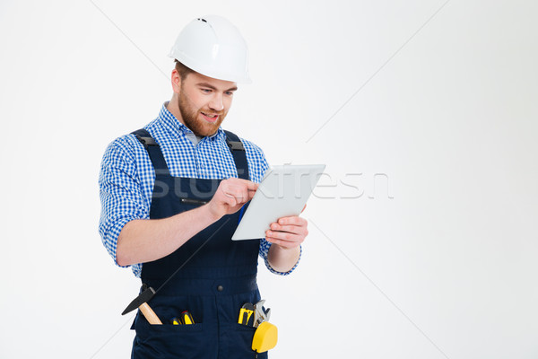 Happy bearded young builder in helmet and overall using tablet Stock photo © deandrobot