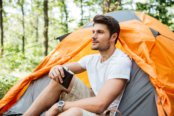 Man tourist with flask sitting at touristic tent in forest Stock photo © deandrobot