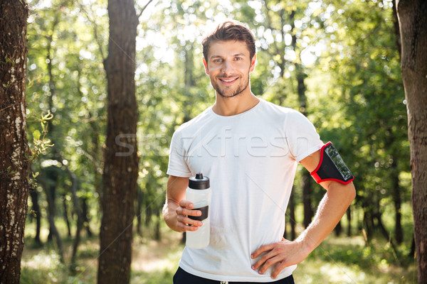 Cheerful young sportsman standing and drinking water in forest Stock photo © deandrobot