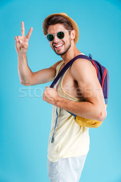 Smiling young man with backpack showing peace sign Stock photo © deandrobot