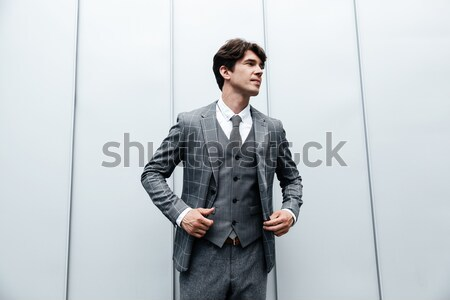 Serious attractive young man standing and pointing to camera Stock photo © deandrobot