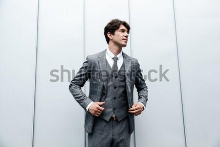 Komoly vonzó fiatalember áll mutat kamerába Stock fotó © deandrobot