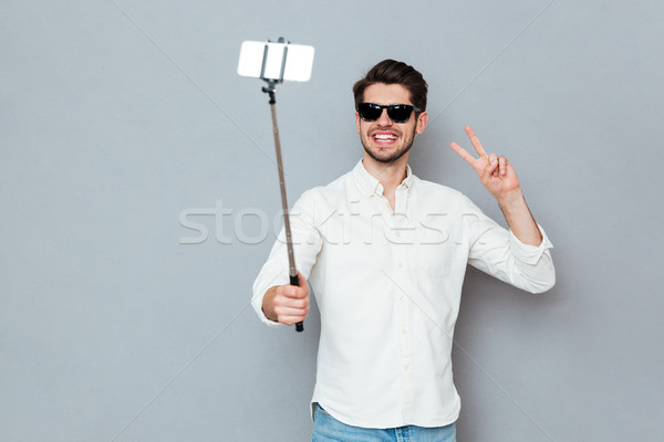 Man wearing sunglasses taking photos with smartphone and selfie stick Stock photo © deandrobot