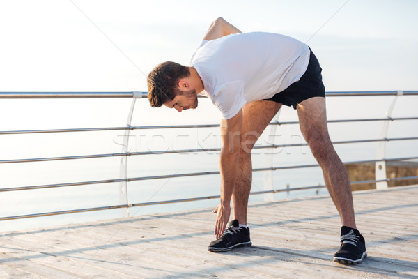 Male athlete doing morning exercises on wooden terrace Stock photo © deandrobot
