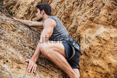 Young man climbing natural rocky wall Stock photo © deandrobot