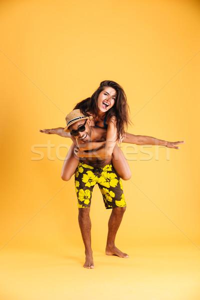 Young happy couple enjoying piggyback ride Stock photo © deandrobot