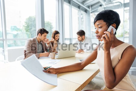 Stock photo: Businesswoman working with documents and talking on mobile phone