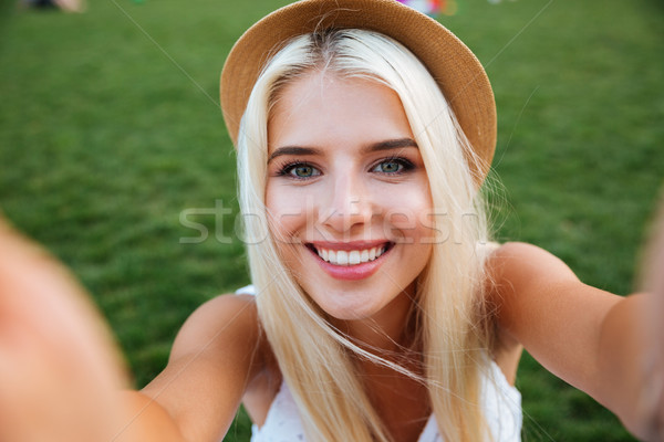 Young smiling cheerful blonde girl in hat making selfie Stock photo © deandrobot