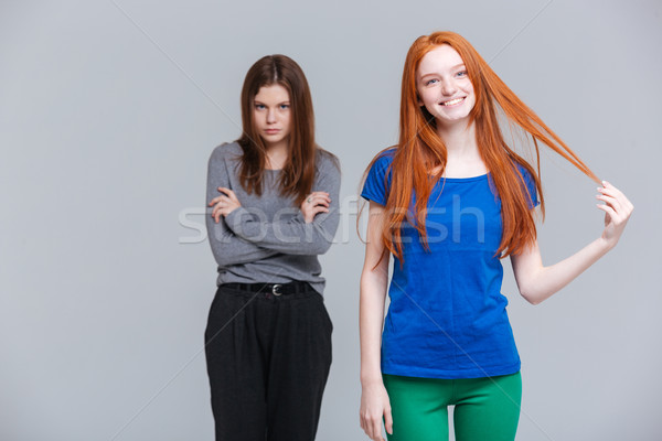 Two smiling redhead and upset brunette young women Stock photo © deandrobot