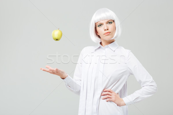 Beautiful woman standing and throwing apple in the air Stock photo © deandrobot