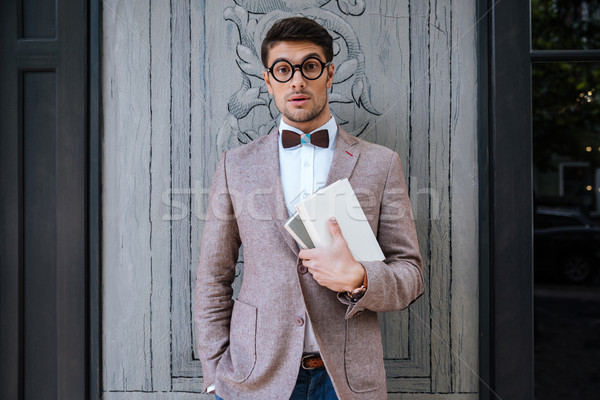 Young fashion man with nerd glasses and stylish hairdo posing Stock photo © deandrobot