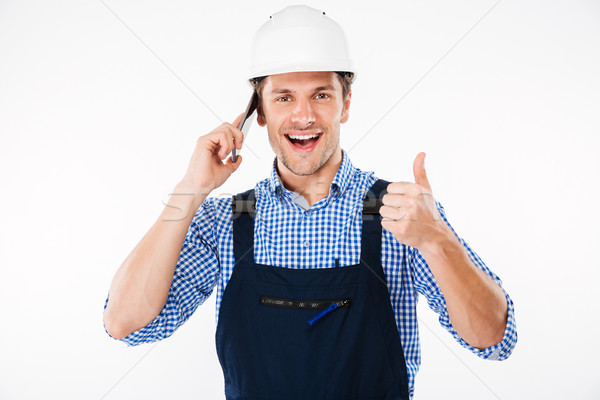 Builder in overall talking on phone and showing thumbs up Stock photo © deandrobot
