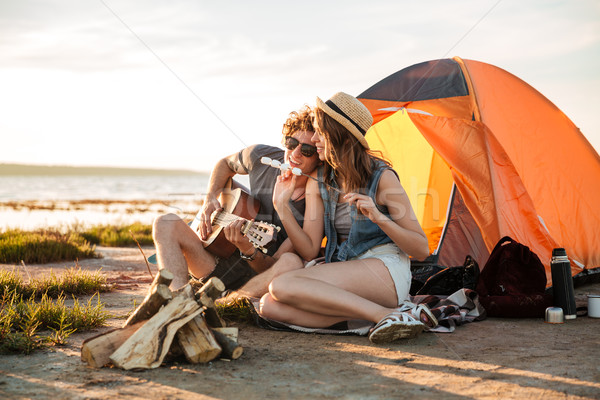 Couple playing guitar and eating fryed marshmallows near touristic tent Stock photo © deandrobot