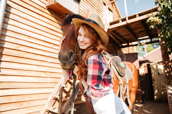 Cheerful woman cowgirl standing and hugging her horse on farm Stock photo © deandrobot