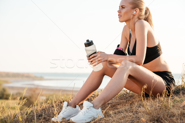 Beautiful young fitness woman relaxing after jogging Stock photo © deandrobot
