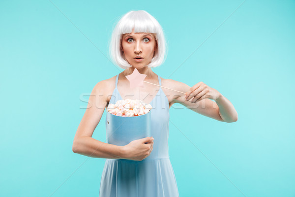 Pretty young woman with marshmallows standing and using magic wand Stock photo © deandrobot