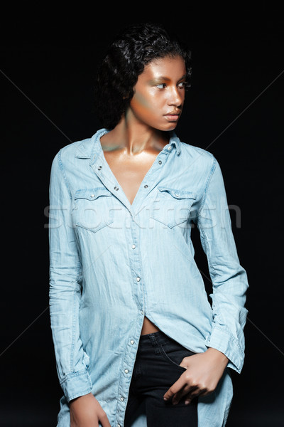 Confident african young woman with shining makeup standing and posing Stock photo © deandrobot