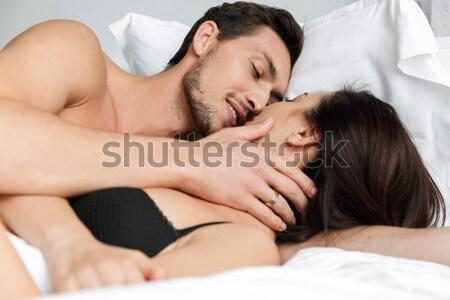 Pretty interracial couple in bed Stock photo © deandrobot