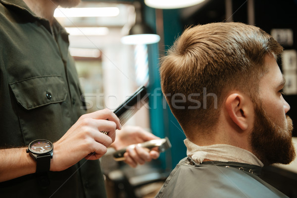 Young man getting haircut by hairdresser with razor Stock photo © deandrobot