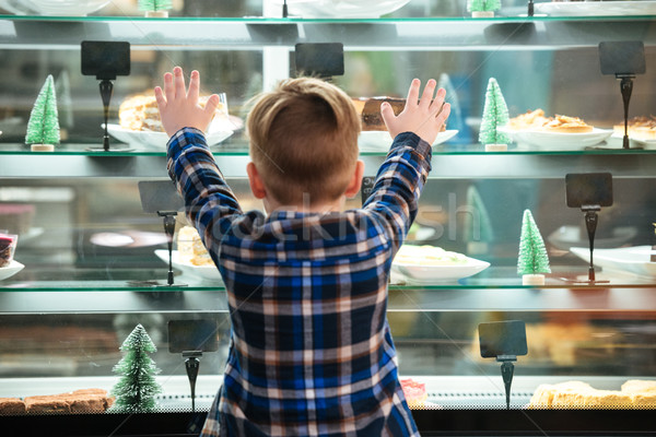 Back view of little boy looking at cakes in showcase Stock photo © deandrobot