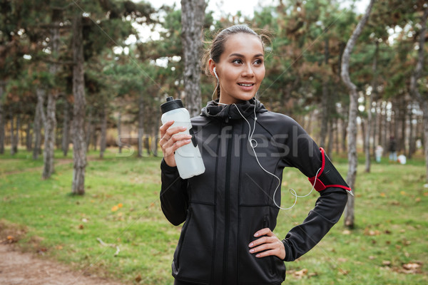 Woman runner looking aside while holding bottle of water Stock photo © deandrobot